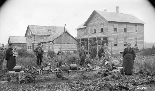 Michael Baltus family posing in front of their log cabin two miles east of Auburndale Station, Wood County, with a new frame house under construction nearby. The table in the foreground is displaying vegetables grown on the farm.