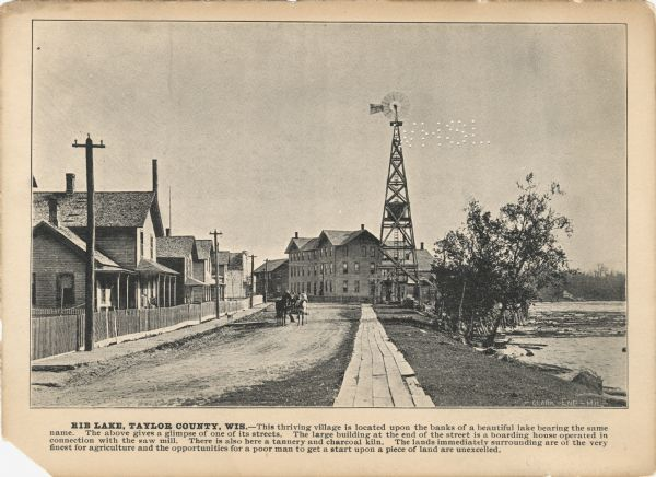 "A promotional card displaying a populated village street near a lake in Northern Wisconsin.<p>The caption bellow the photography reads: ""RIB LAKE, TAYLOR COUNTY, WIS. — This thriving village is located upon the banks of the beautiful lake bearing the same name. The above gives a glimpse of one of its streets. The large building at the end of the street is a boarding house operated in connection with the saw mill. There is also here a tannery and charcoal kiln. The lands immediately surrounding are of the very finest for agriculture and the opportunities for the poor man to get a start upon a piece of the land are excelled."