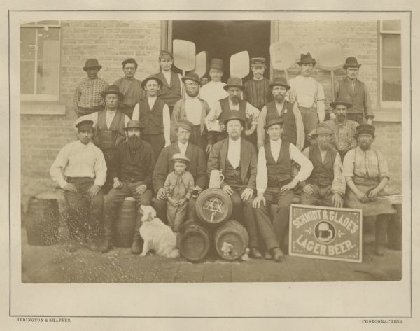 Group portrait of workers, a young boy and a dog outside the Schmidt and Glade Brewery posing with tools and barrels.