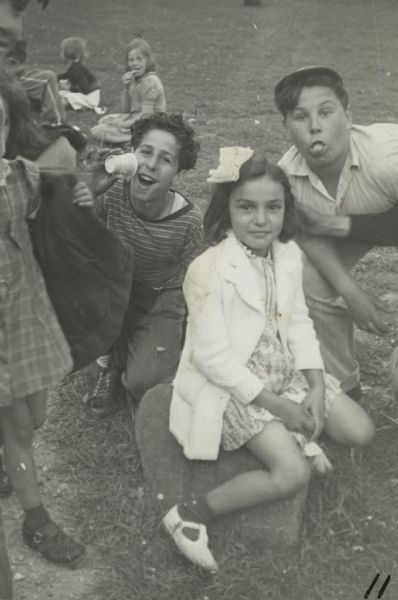 Image from a scrapbook kept by Neighborhood House, with Mary Vultaggio sitting on a rock with two boys behind her who are clowning for the camera (Frank Romano is sticking out his tongue, and other children around them on the grass.