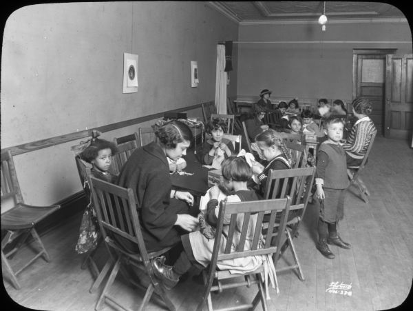 Groups of children seated at tables for a Saturday morning sewing group at Neighborhood House, with a woman helping the children at each table. One boy is standing and looking off to the side. A girl seated in the foreground appears to be looking at the camera.