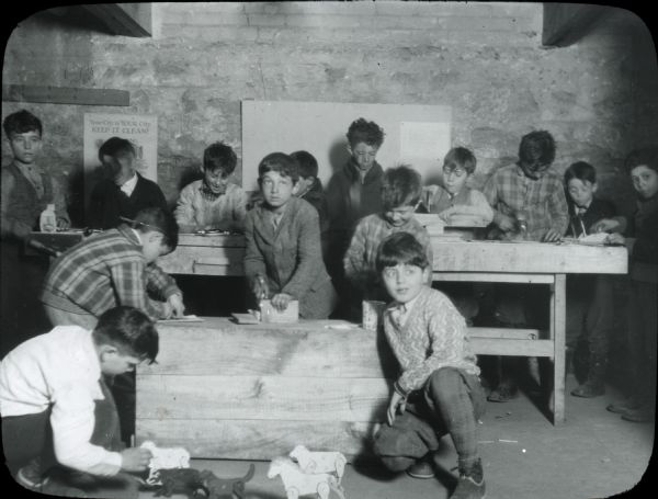 Boys working on various stages of woodwork projects, with two boys in the foreground kneeling by some wooden toy animals with jointed limbs. The settlement house sponsored various craft activities for children.