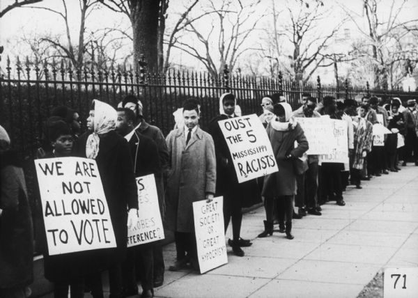 A large line of protesters holding signs calling for voting rights and civil rights stand on a sidewalk along a fence.
