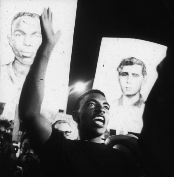 A young man at a nighttime rally (perhaps at a demonstration during the Democratic National Convention in Atlantic City) in support of the MFDP. Behind him people carry placards with portraits of James Earl Chaney and Andrew Goodman, two of the three civil rights volunteers who were murdered during Freedom Summer of 1964.