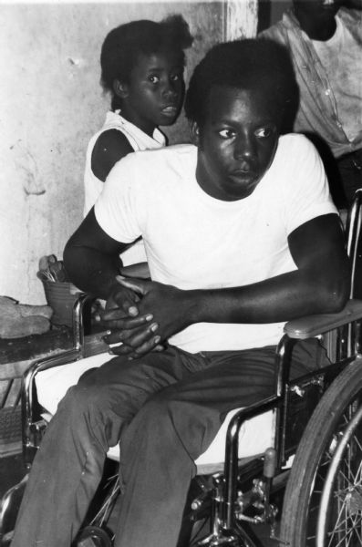 A young man is seated in a wheelchair. Behind him is a young girl and another person standing in a doorway. This image comes from the papers of Dorothy Zellner, civil rights activist and SNCC (Student Nonviolent Coordinating Committee) staff member.