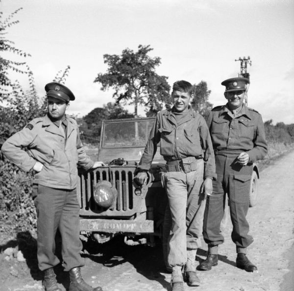 "A roadside stop in Normandy, France. Three men are standing with a jeep. From left is Robert Doyle, war correspondent for the <i>Milwaukee Journal</i>. The other men are Eric Baume, Australian correspondent and London Bureau Chief for <i>Truth Newspapers</i>, and Edward Chichester, the 6th Marquess of Donegall, ace reporter for the <i>London Sunday Dispatch</i>. A helmet is attached to the grill of the jeep with the name, ""T.S. Rat"" stenciled on it. Trees and shrubs are on the side of the road."