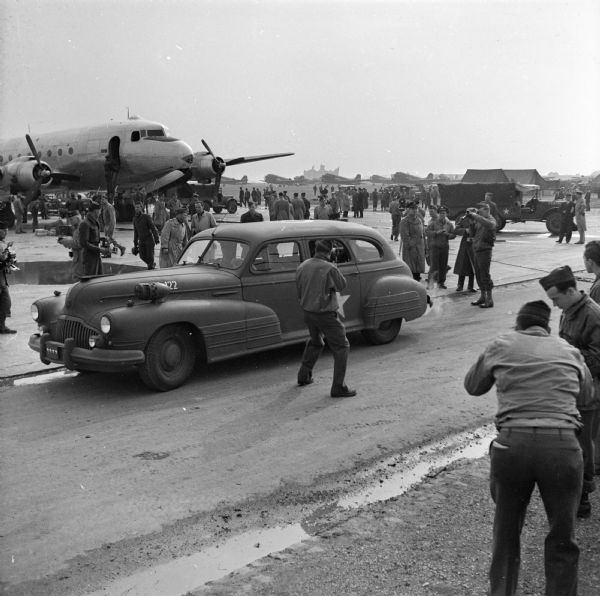 """Many photographers take photos of a military automobile leaving an airfield in Paris, France. Robert Doyle notes """"arrival of first plane US ATC (United States Air Transport Command) to fly direct from America today."""" On that plane were General George C. Marshall and Justice James F. Byrnes who were met by General Dwight D. Eisenhower and General George C. Marshall. The plane, on the left, is a Douglas C-54 Skymaster. In the background are jeeps, more airplanes and a group of spectators."""