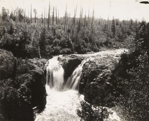 Elevated view of Copper Falls on the Bad River. Four people, one man and three women, are posing on rocks at the top of the falls. Surrounding burned-over forest area.
