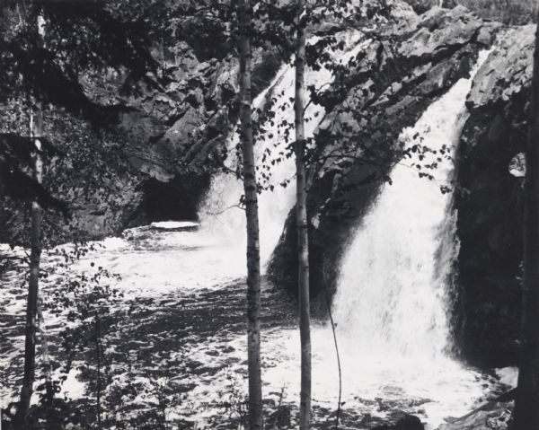 View through trees of Copper Falls, on the Bad River.