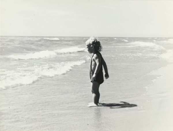 Small child standing on the shoreline of a sandy beach, looking out at  the waves, at Terry Andrae State Park on Lake Michigan.