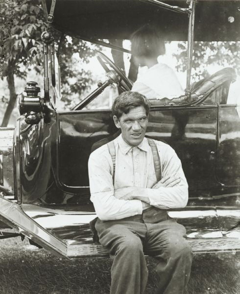 View of a man, who is apparently blind in one eye, sitting on the running board of a Model T Ford touring automobile outdoors. A young girl is sitting in the driver's seat.