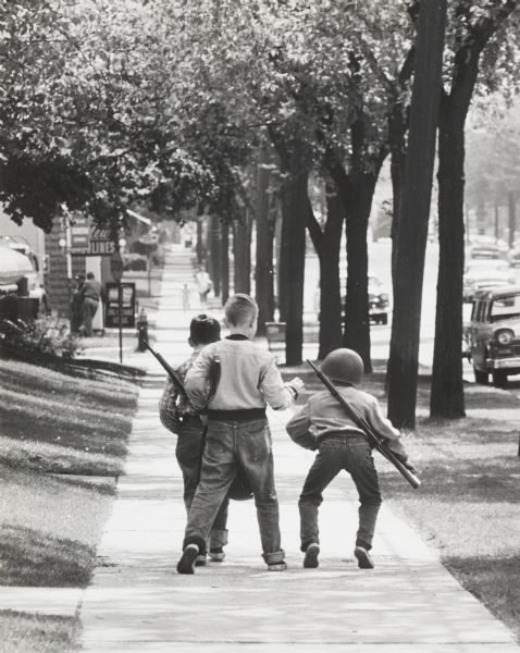 "Residential street with three boys playing ""soldier""."