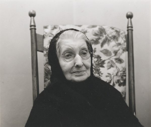 Head and shoulders portrait of an unidentified elderly woman, wearing a shawl, seated in an antique chair.