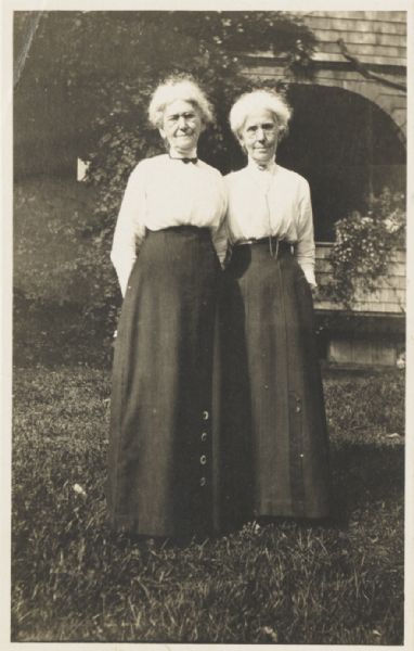 Portrait of Ellen Lloyd Jones and her sister Jane Lloyd Jones standing in front of the Hillside School which they founded and managed. Both sisters wear eyeglasses, high-collared white blouses, and long dark skirts. The Lloyd Jones sisters were aunts of the noted architect Frank Lloyd Wright.