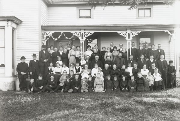 Outdoor group portrait of some eighty members of the extended Meinen family on the occasion of the golden anniversary of two of its members. They are standing on and around the porch of a house.