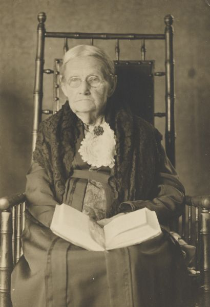 Portrait of elderly woman seated in a chair, holding a book in her lap.