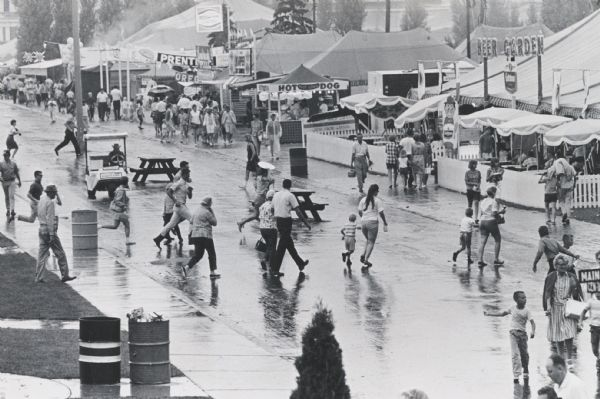 Visitors to the Wisconsin State Fair running for shelter at the onset of a sudden rain shower.