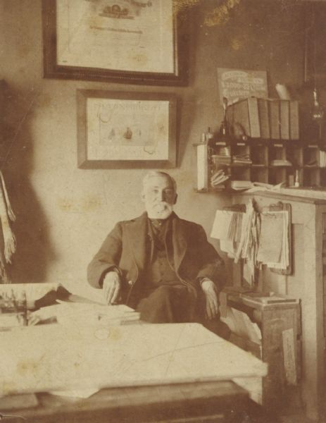"Informal portrait of ""Captain Boyd"" seated in what appears to be an office."