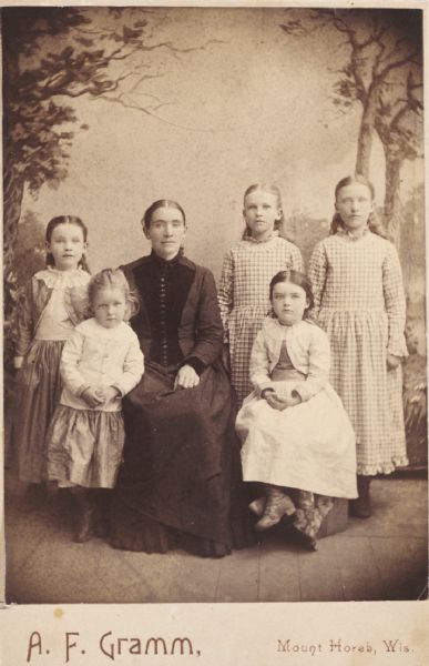 Posed group studio portrait in front of a painted backdrop of Mrs. Cuneen and her five daughters. From left to right: Mamie, Nora, Katie, Annie, and Daisy.