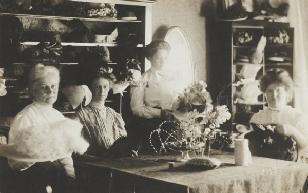 Mrs. Rossing's millinery shop. Left to right: Mrs. Rossing, Viola Rossing, Anna Davis and the trimmer.