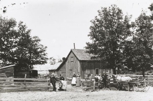 Family posed at gate of farm, with farm buildings in the background. Two men stand with a horse-drawn cart on the right.