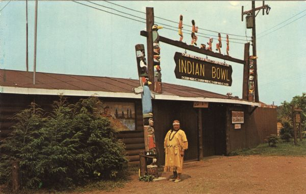 "View of the exterior of the ""Indian Bowl,"" a venue for powwows. A Native American woman is standing in front next to the totems."