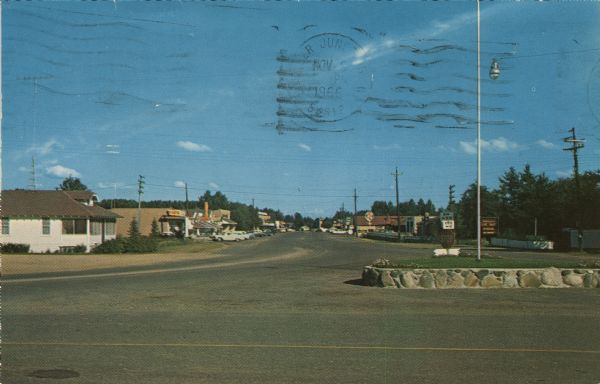 View of the commercial district. Cars are parked in front of businesses. A flagpole and a stop sign are on a highway island in the foreground.