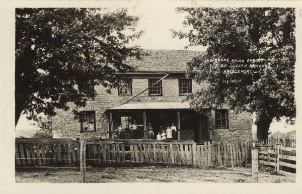 Photographic postcard view of a stone house with a group of people standing on the porch. Wood and barbed wire fencing is in the front yard.