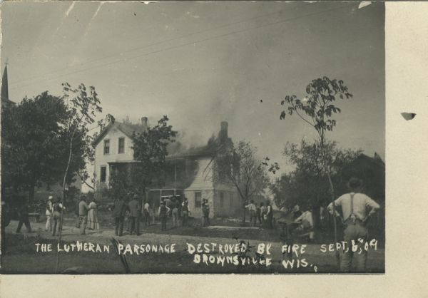 Photographic postcard view of the aftermath of a fire. Most of the parsonage is destroyed. There are onlookers on the lawn in front of the house.