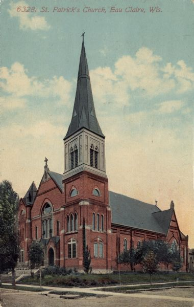 Colorized postcard of a corner view of St. Patrick's Church. The church has a steeple and bell tower to the right of the entrance.