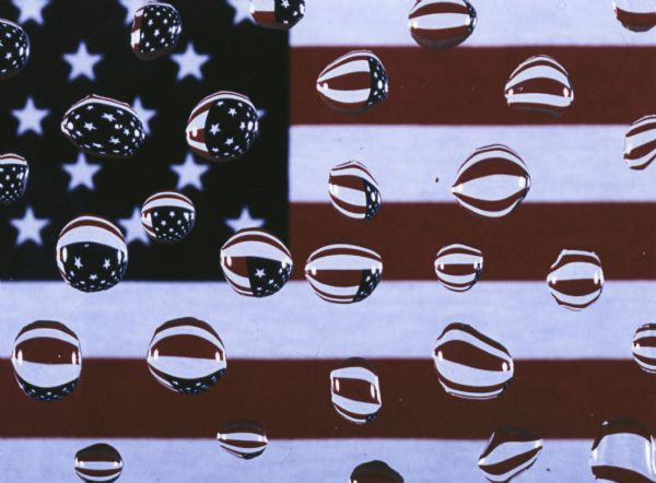 Water droplets capture the image of the American flag.