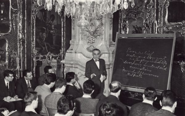 Arthur Altmeyer standing at a blackboard speaking at the Salzburg seminar in American studies.<p>Arthur J. Altmeyer (1891–1972) was the United States Commissioner for Social Security from 1946 to 1953, and chairman of the Social Security Board from 1937 to 1946. He was a key figure in the design and implementation of the U.S. Social Security system.