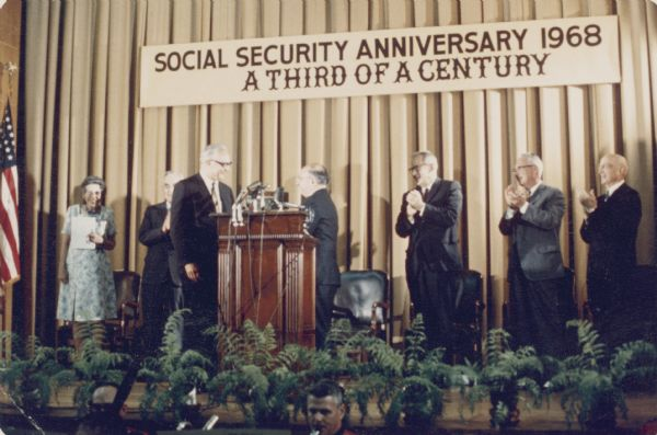 Robert Ball and Wilbur Cohen stand at the lectern during a celebration of the anniversary of Social Security. Robert Ball was Commissioner of Social Security from 1962 until 1973; Wilbur Cohen from 1935 to 1956. Both men maintained active advocacy of social security throughout the rest of their careers.