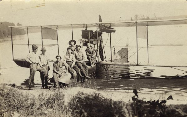View from shoreline of Trout Lake of a group of six men posed with the pilot, possibly Jack Vilas, on an early seaplane or flying boat floating in the water at the shoreline. The six men are dressed in work clothes and hats.<p>This is an early use of an aircraft to detect forest fires.