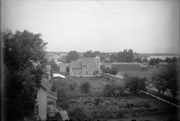 "Elevated view of houses and yards on Main Street between 2nd and 3rd Avenues. There is a large white house with a tower is the family home of the Walters who own the ""pop"" factory. A brick structure, the Scott Store, is across Main Street, one of the first in Wisconsin. Trees line the street and mark the boundaries of the Walters' yard. In the background is a bridge over a lake."