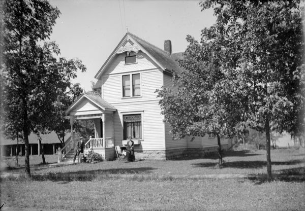 View across front lawn of family posed in yard of house located on S. 3rd Street. Otto Ansorge leans on the bannister of his front porch. An unidentified woman (probably his wife) stands in front of the house's front window besides a baby sitting in a stroller. There are trees in the yard, and a board sidewalk in front of the house. Behind the house on the left is a shed or garage.
