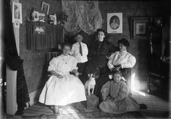 The Bardes Family poses in their home. Family members pictured include (left to right): Nora, Jerry, Alice, Mrs. Bardes, and Barbara. The portrait also includes the family dog sitting in the middle on a footstool. The room is decorated with wallpaper, lace, and various portraits. The home belonged to Don Bardes (not pictured), a barber.