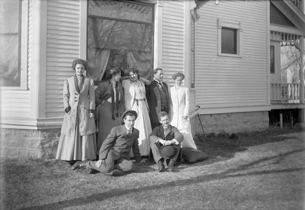 Four women and three men pose outdoors along the side of Otto Ansorge's house. They include (standing, left to right): Mrs. Ansorge, two unidentified women, George Miller, and Miss Edna Hudson, a teacher. Seated in front on the grass are, left to right: Otto Ansorge, and an unidentified man. George Miller was a local banker and Otto Ansorge was a jeweler.
