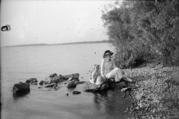 Wearing a long, white dress, white shoes and a large, ribboned hat, Mary Ansorge poses on a large stone on the rocky bank of Lake Winneconne. Her daughter, Betty, sits on a stone beside her, smiling and holding a large straw hat on her knees. Dense foliage is on the right. The distant shore of the other side of Lake Winneconne is in the background.