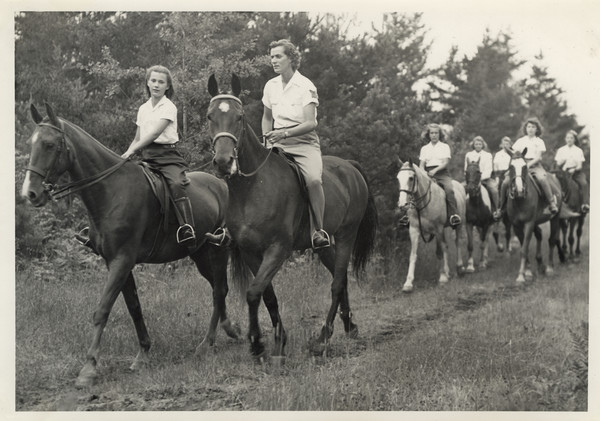 "Group of campers and a camp counselor riding on horseback on a trail in wooded area. Original caption notes: ""Riding is one of the most popular sports. English style of riding is taught, and complete at-home-ness on the horse is emphasized. The girls also learn how to saddle and bridle, and take general care of their mounts. Each horse is carefully selected, and all are three-gaited. We have a ring on the camp site, and hundreds of miles of woods trails available to us."""