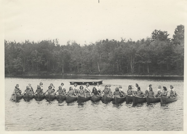Large group portrait of campers and counselors sitting in a row of fourteen Joy Camps canoes, side-by-side in a lake. A raft floats in the water behind them. For a complete description of the Joy Camps fleet of boats, see Image ID 108160.