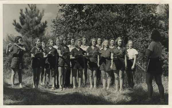 "Joy Camps choir, consisting of counselors and campers in camp uniform, posing standing outdoors in two rows. Several campers are holding music books open. A camper to the far left is playing a flute. To the far right a counselor stands with her back to the camera, and appears to be in charge of the group. The choir stands in a sunny, grassy area adjacent to woods. Original caption notes: ""Our Camp Choir, under the supervision of a graduate in Music Education, is one of the most enjoyed of all our camp activities. Sunday visitors to our Services will attest to this fact."""