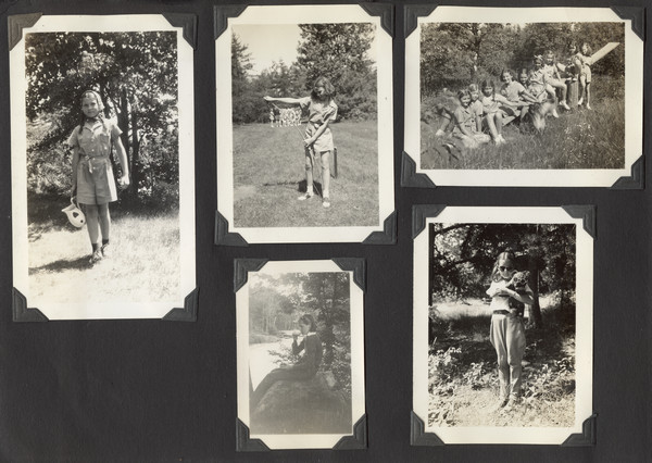 "Page from Joy Camps photo album displaying five photographs. Young campers are captured in various activities, all near wooded areas. One camper in one photograph is holding a stuffed animal; both the camper and the toy are wearing sunglasses. Another camper is bending a bow for archery. Another photograph has a number of campers sitting on a seesaw; some of the campers are petting a dog. Original caption notes that these younger campers were part of Joy Camps ""Camp Pioneer."""