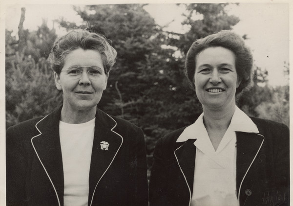 "Outdoor quarter-length portrait of Joy Camps co-directors, Barbara Ellen Joy (on the left) and Marjorie Camp (on the right). Both women are wearing white shirts and matching dark jackets. Miss Joy also has a pin attached to one of the lapels of her jacket. A wooded area is in the background. Back of photograph carries stamp: ""Minocqua Photo Shop, Victor A. Hendrickson, Minocqua, Wis."""