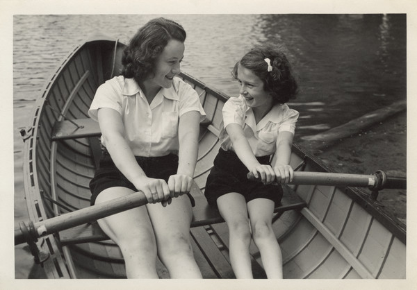 Close-up of a camp counselor and young camper in a rowboat on the water. They are looking at each other and smiling. Both are wearing white shirts and dark colored shorts.