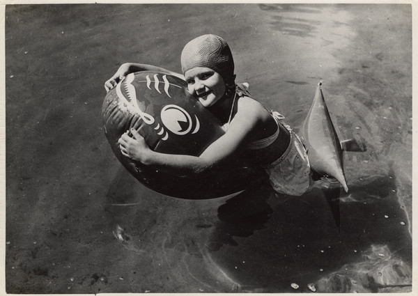 A young camper in swimsuit and swimming cap holds onto a floating device shaped like a fish, while floating in the water.