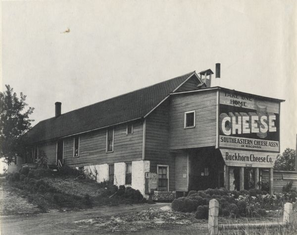 "Exterior view of the Buckhorn Cheese Company plant. A sign painted on the exterior of the building reads: ""Take One Home."""