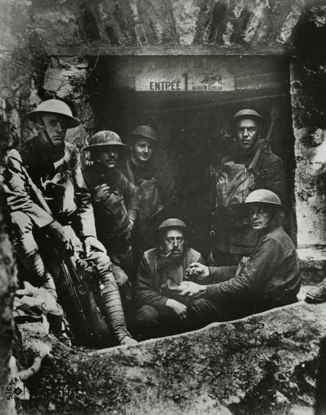 "Allied soldiers gathered near an entrance to an unknown establishment. A sign in French above the entrance is not legible, but there is an image of a cricket and the words: ""Le Grillon."" The man squatting in the middle is smoking a pipe, and the man next to him appears to be holding a grenade in each of his hands."