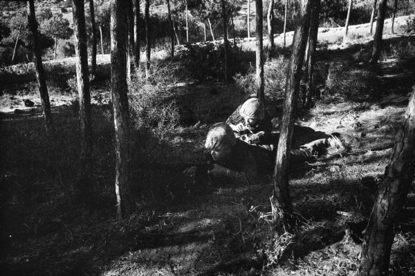 Dickey Chapelle in Lebanon wearing camouflaged clothing and a helmet crouched low to the ground and holding a camera. She is next to and behind a soldier who is laying flat on his stomach in a sparsely wooded area with a rifle aimed to the left.