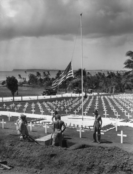 The cemetery for the war dead on Guam. The body of a fighting man who died of wounds received during the battle for Iwo Jima is being lowered into the earth. In the background trees are along a shoreline, and a far shoreline is in the distance.